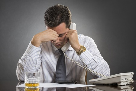 Stressed businessman in white shirt having a bad headache while talking on the telephone against grey , Glass of alcohol on desk. photo