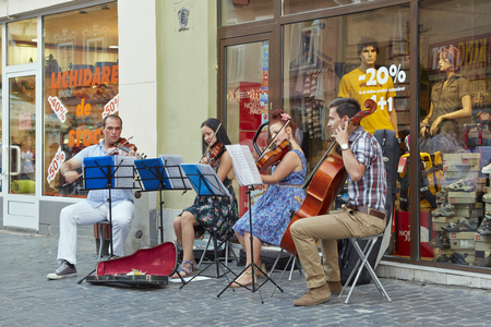 BRASOV, ROMANIA - JULY 14: Unidentified string quartet artists play chamber music on July 14, 2013 in Brasov, Romania. Buskers perform for tourists on the streets of historical center of Brasov. Sajtókép