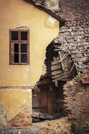 Detail of an old abandoned ruined house with shattered tile roof and cracked brick wall.