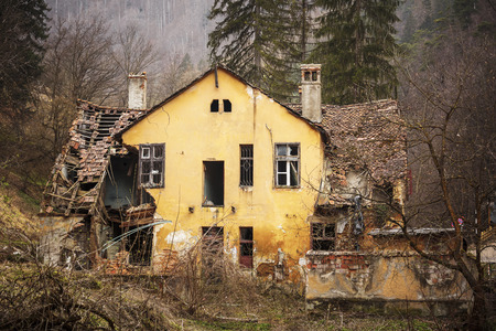 devastation: Old abandoned ruined house with shattered roof and broken windows, in the forest up in the mountains.