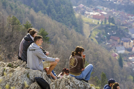 BRASOV, ROMANIA - MARCH 23: Group of unidentified young people sit on top of Tâmpa Mountain and enjoy city panorama on March 23, 2014 in Brasov, the largest city in a mountain resorts area in Romania.