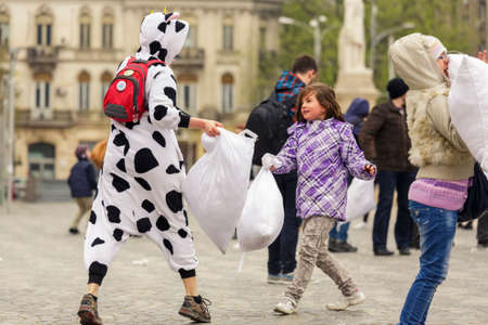 BUCHAREST, ROMANIA - APRIL 5: Unidentified young girl and woman in clown costume enjoy a pillow fight on International Pillow Fight Day on April 5, 2014 in University Square, Bucharest, Romania.