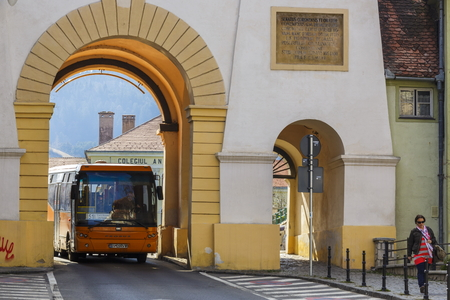 buss: BRASOV, ROMANIA - MARCH 23: Unidentified woman and orange buss pass beneath the Schei Gate on March 23, 2014 in Brasov, Romania. The Schei Gate was built in between 1827 and 1828.