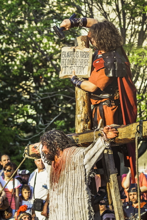 reenact: BUCHAREST, ROMANIA - MAY 3: Unidentified men playing Jesus and Roman soldier reenact the crucifixion of Jesus Christ during the Way of the Cross on May 3, 2013 in Bucharest, Romania.