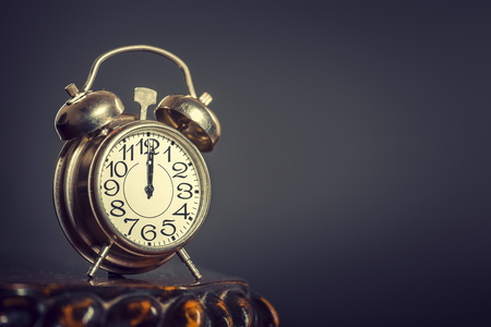 Old alarm clock showing twelve o clock over dark background