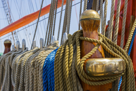 Rows of ropes hanging on large wooden and metal pegs on ancient sailing vessel board. Shallow depth of focus. photo