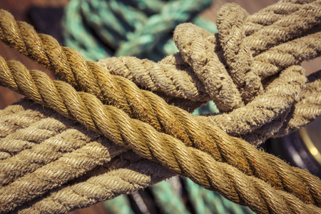 Close-up of used vintage marine ropes with nautical knot on old sailing vessel. photo