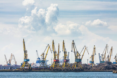dockside: CONSTANTA, ROMANIA - MAY 27, 2014: Industrial port quay with heavy load dockside cranes recycling iron and steel waste in Constanta port, the largest on the Black Sea and the 18th largest in Europe.