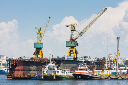 keel: CONSTANTA, ROMANIA - MAY 27, 2014: Docked towboats  and heavy loadport cranes in the shipyard of commercial port of Constanta, the largest port on the Black Sea and the 18th largest in Europe. Editorial
