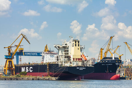 ship bow: CONSTANTA, ROMANIA - MAY 27, 2014: Bulk cargo ships docked under crane bridge in industrial port quay of Constanta, the largest on the Black Sea and the 18th largest in Europe.