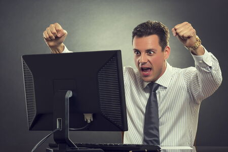 great deal: Excited businessman shouting of joy and gesturing with raised clenched fists over successful business deal in front of a computer over dark grey .