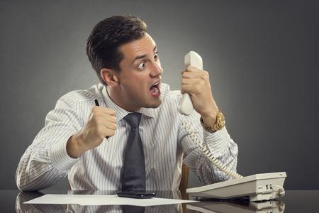 白いシャツとネクタイは仕事で電話での会話中に怒り爆発している猛烈な実業家。衝動的な実業家叫んで、電話中に激怒顔ゆがんだ顔を見せてしま
