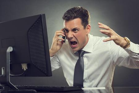 白いシャツとネクタイ叫びと灰色の背景に対してコンピューターのディスプレイの前に携帯電話の会話中に身振りで示すことで怒っているビジネス