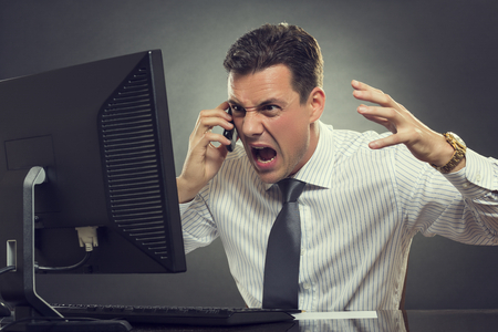 Angry businessman in white shirt and necktie shouting and gesturing during cellphone conversation in front of a computer display against grey background.