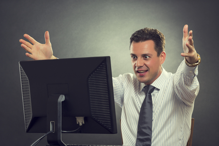 Portrait of thrilled businessman in white shirt and necktie gesturing with his raised hands over successful business, great news or brilliant idea in front of a computer over grey background. photo