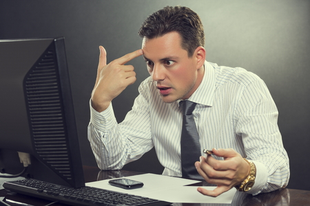 若い絶望的なビジネスマンに衝撃を与えた白いシャツとネクタイは撮影で彼の頭に彼の指を指している彼自身の仕事で彼のコンピューターの前に破