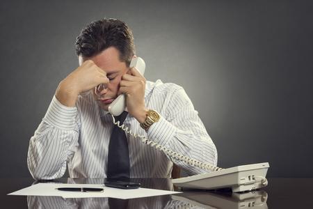 白いシャツとネクタイの緊張に満ちた電話での会話中に頭痛を有する圧倒されるビジネスマン。片方の手で彼の額に退屈な電話を取って疲れている