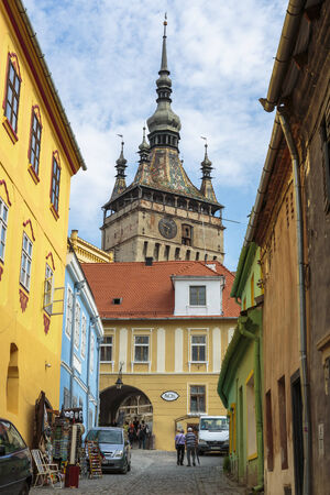SIGHISOARA, ROMANIA - JULY 26, 2014: Clock tower and colorful houses in medieval citadel of Sighisoara, listed by UNESCO as World Heritage Site. Vlad Tepes (Dracula) was born here in 1431.