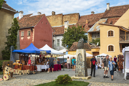 SIGHISOARA, ROMANIA - JULY 26, 2014: Unidentified tourists visit traditional craft market in the citadel of Sighisoara, one of the few still inhabited citadels in Europe, UNESCO World Heritage Site.