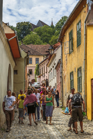 SIGHISOARA, ROMANIA - JULY 26, 2014: Unidentified tourists stroll the old streets of the medieval citadel of Sighisoara, a UNESCO World Heritage Site and birth place of Vlad Tepes (Dracula) in 1431.