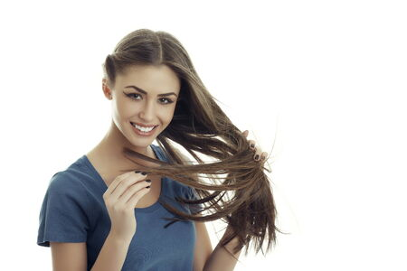 long silky hair: Portrait of a beautiful positive woman smiling at you while playing with a strand of her long silky hair, isolated on white. Stock Photo