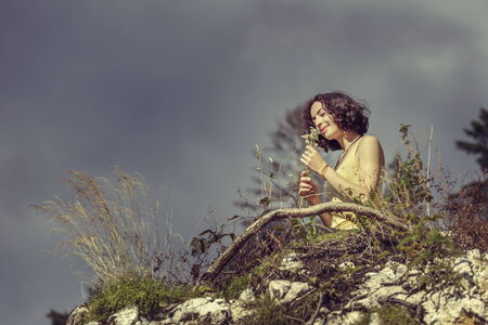 Beautiful happy redhead woman smelling a bouquet of wild mountain flowers while relaxing on top of a rock. photo