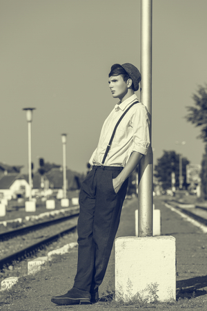 rolled up sleeves: Thoughtful young guy with hand in pocket and rolled up sleeves, wearing hat and trousers with suspenders, leaning his back against a street lamp post while waiting on a railway platform. Monochrome. Stock Photo