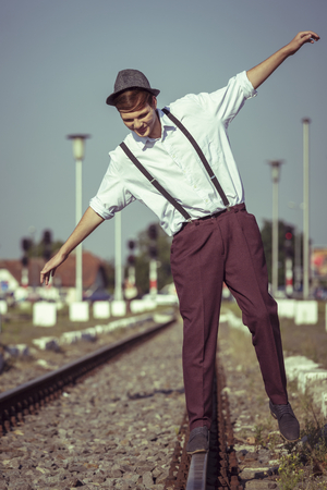 Joyful young fellow in white shirt with rolled up sleeves, hat and trousers with suspenders, trying to maintain his balance on a rail beside a railway platform. photo
