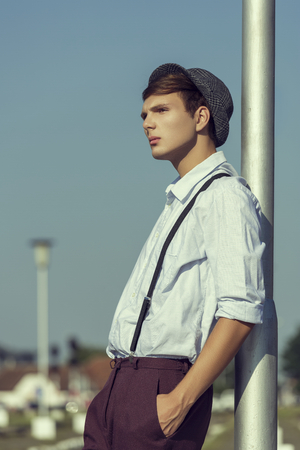 his shirt sleeves: Side view of a thoughtful young guy posing with hand in pocket and rolled up sleeves, wearing hat, shirt and trousers with suspenders, looking away while leaning his back against a street lamp pillar. Stock Photo