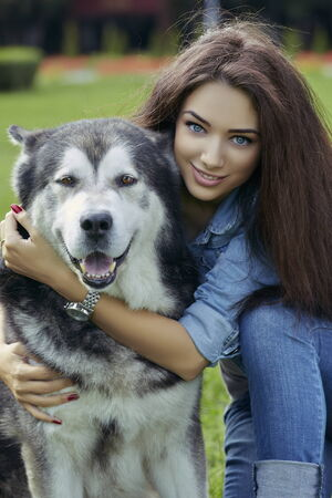 Portrait of gorgeous smiling young lady with blue eyes, long hair and wearing blue jeans hugging a big Alaskan Malamute male dog while looking at the camera. photo