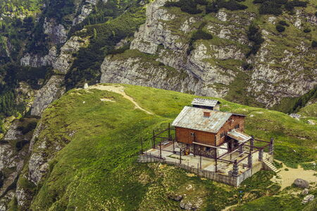 refuge: Old weathered chalet on top of steep cliff in Bucegi mountains, Romania. Desolate abandoned wooden mountain refuge.