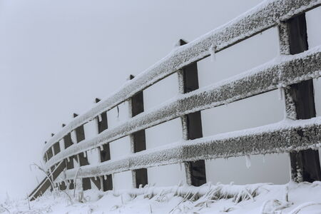 Frozen wooden fence covered by snow and frost in a freezing foggy winter morning. Stock fotó
