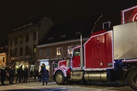 towed: BRASOV, ROMANIA - DECEMBER 11, 2014: Unidentified people come to see the Red Christmas Coca-Cola truck visiting the Council Square (Piata Sfatului) of Brasov city, Romania at night. Editorial