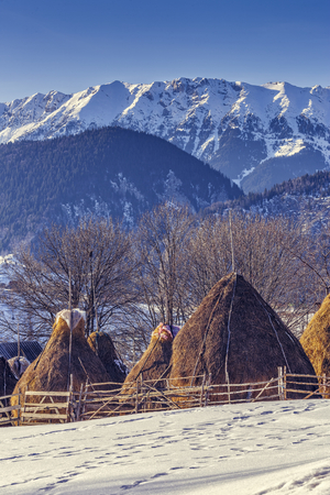Winter rural landscape with traditional Romanian farm with sheep pen and haystacks near Piatra Craiului massif in Magura village, Brasov county, Romania. photo