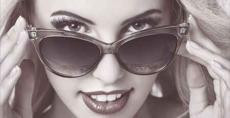 grading: Closeup portrait of a beautiful smiling woman giving a seductive hypnotic look over dark sunglasses. Monochrome mate tinted color grading. Stock Photo