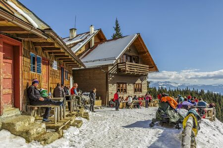 adventurers: PIATRA CRAIULUI, ROMANIA - FEBRUARY 14, 2015: Unidentified travelers relax and enjoy a winter sunny day at the old wooden Curmatura chalet at 1470m altitude in Piatra Craiului National Park. Editorial
