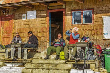 hospedaje: Piatra Craiului, Rumania - 14 de febrero 2015: los turistas no identificados descansar en el porche de una vieja cabaña de madera de alojamiento en Curmatura chalet en la altitud 1470m en el Parque Nacional de Piatra Craiului.