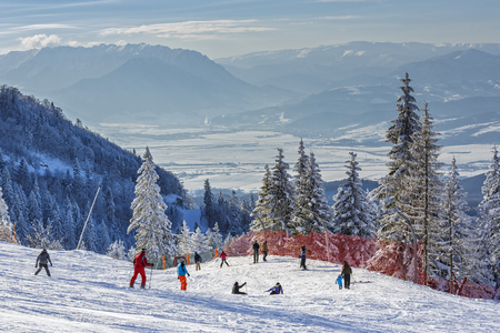 ski runs: POIANA BRASOV, ROMANIA - FEBRUARY 11, 2015: Unknown group of skiers descend the ski slopes in Poiana Brasov, the most famous Romanian winter resort, in Postavaru Mountain, Brasov county. Editorial