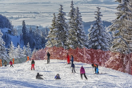 ski runs: POIANA BRASOV, ROMANIA - FEBRUARY 11, 2015: Unknown group of skiers enjoy the ski slopes in Poiana Brasov, the most appreciated Romanian winter resort, in Postavaru Mountain, Brasov county.