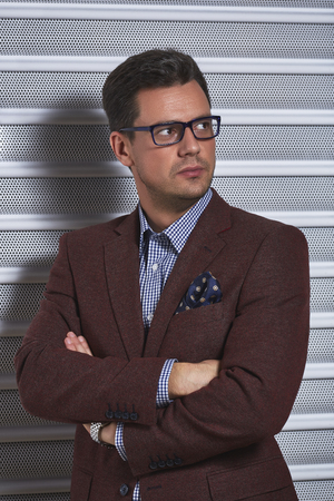 checked shirt: Confident stylish handsome gentleman posing with crossed arms, wearing spectacles, checked shirt and brown suit jacket with handkerchief in pocket over grey metal textured background.