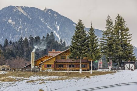 PREDEAL, ROMANIA - FEBRUARY 19, 2015: Rustic wooden Poiana Secuilor chalet with smoking chimney in an overcast winter morning at 1070m altitude. Postavaru mountain (1799 m altitude) in the background.