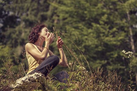 Beautiful peaceful redhead woman gently touching and smelling wild mountain plants while resting on top of a rock. photo