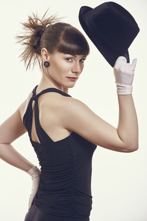 ravishing: Portrait of gorgeous stylish woman wearing dark clothing with bare shoulders and arms, saluting with dark hat while looking at camera over bright background. Stock Photo