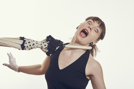 pulled over: Beautiful frightened stylish young woman screaming in despair while pulled aside with umbrella handle around her neck over bright background. Stock Photo