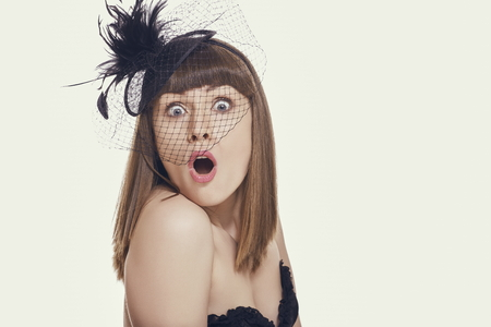 stunned: Stunned young woman making big eyes and jaw drop facial expression while wearing hair accessories with net against bright background. Stock Photo