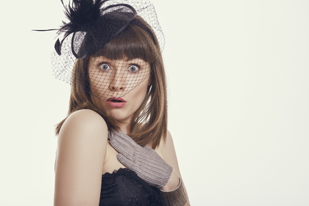 perplexed: Portrait of a startled young woman with perplexed clueless questioning facial expression wearing light feather hat net and gloves against bright background