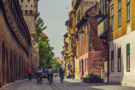 fortified wall: SIBIU, ROMANIA - 06 MAY, 2015: Unidentified tourists enjoy a city tour on bike along the medieval fortified wall with defense towers in upper town of Sibiu city, Transylvania region, Romania. Editorial
