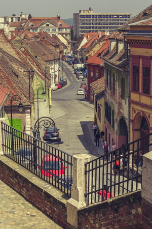 stroll: SIBIU, ROMANIA - 06 MAY, 2015: Unidentified people stroll the cobblestone streets in the medieval Lower Town, developed around the earliest fortifications, bounded by city walls and defense towers.