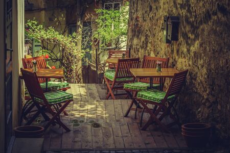 Homey outdoor cafe terrace setting with wooden chairs and tables in a shady vintage place.