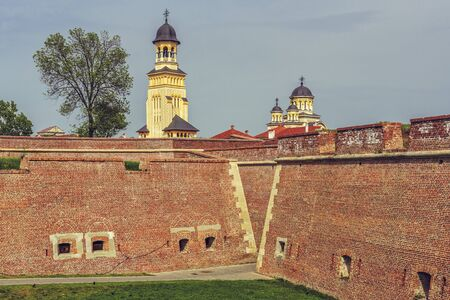 steeples: ALBA IULIA, ROMANIA - MAY 6, 2015: The Coronation Orthodox Cathedral towers and steeples as seen over the fortified walls of Alba Carolina Fortress. The cathedral was built in 1921-1922.